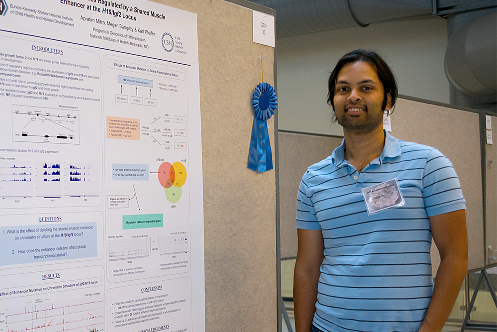 Apratim Mitra stands next to his prize-winning poster