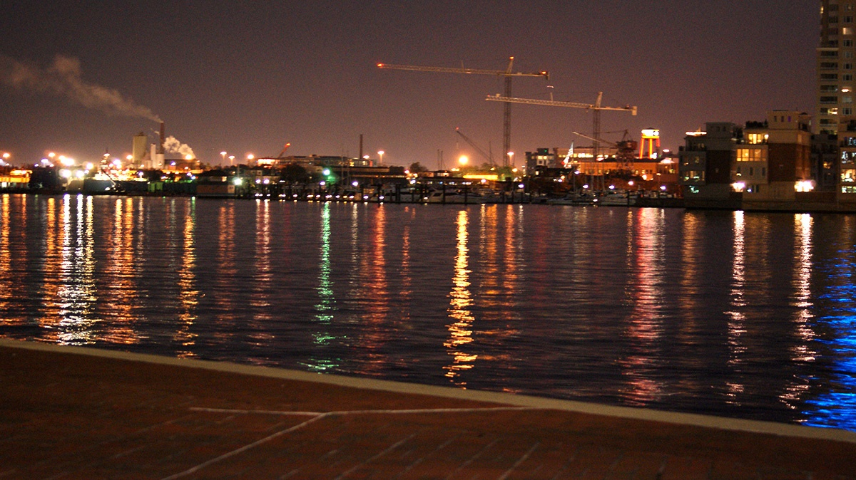 A photo of the Baltimore Harbor at night with lights reflecting on the water