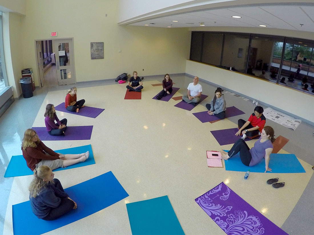 Parents and children sit in a circle on blue and purple yoga mats