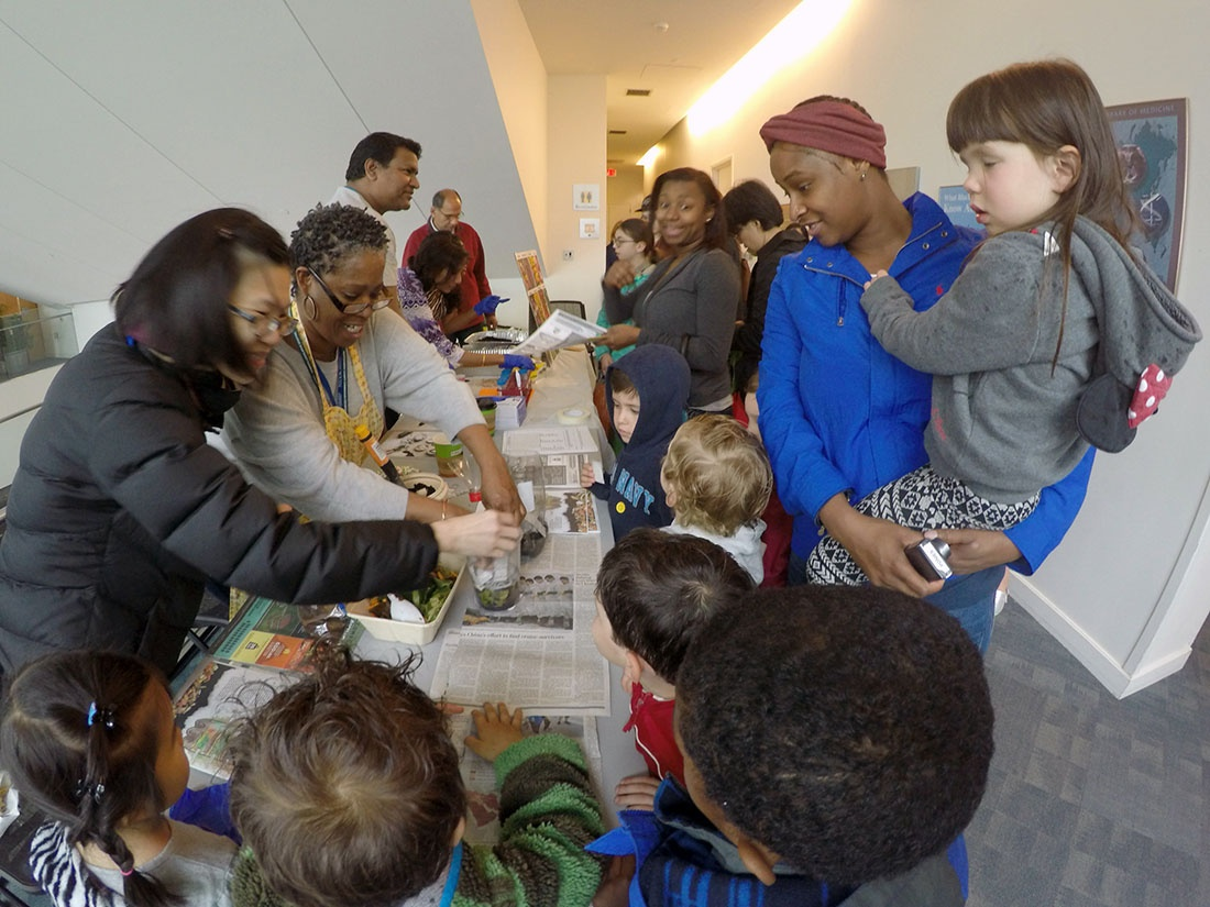 Parents and children look on as the NICHD Green Team demonstrates seed planting