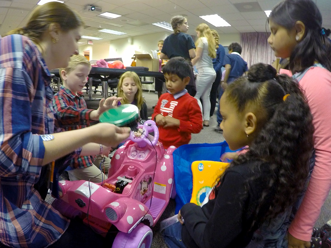 Children and an NIH employee engage with a pink Minnie Mouse ride-on toy