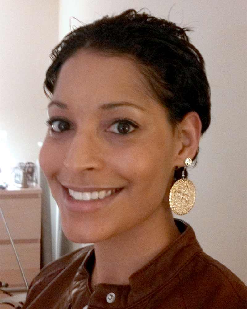 Dr. Blatch smiling, wearing a dark red blouse and gold disc earrings