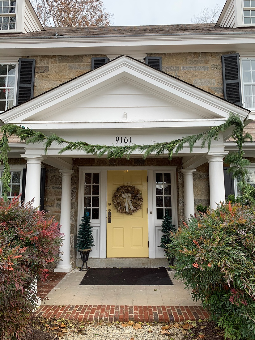 Yellow front door of the FAES house with a wreath and fir garland