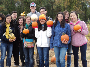 Fellows at Butler's Orchard holding pumpkins and other gourds