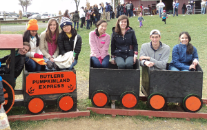 Fellows posing while riding on a kiddie train
