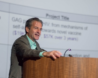 Dr Stratakis in a tweed jacket at a wooden podium with a presentation slide projected on the screen behind him