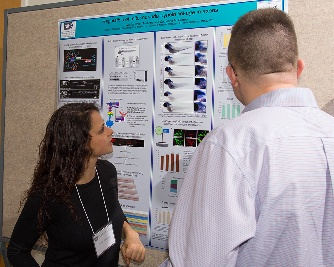 Fellow Wesley Schnapp explains her poster to another retreat attendee