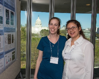 Karen Plevock Haase and Adrienne Perkins next to a research poster with the Capitol in the background