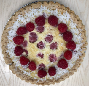 Pie topped with coconut and a ring of raspberries