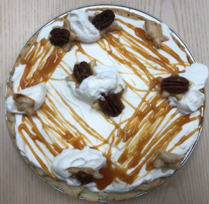 White pie topped with caramel drizzle and turtle candies
